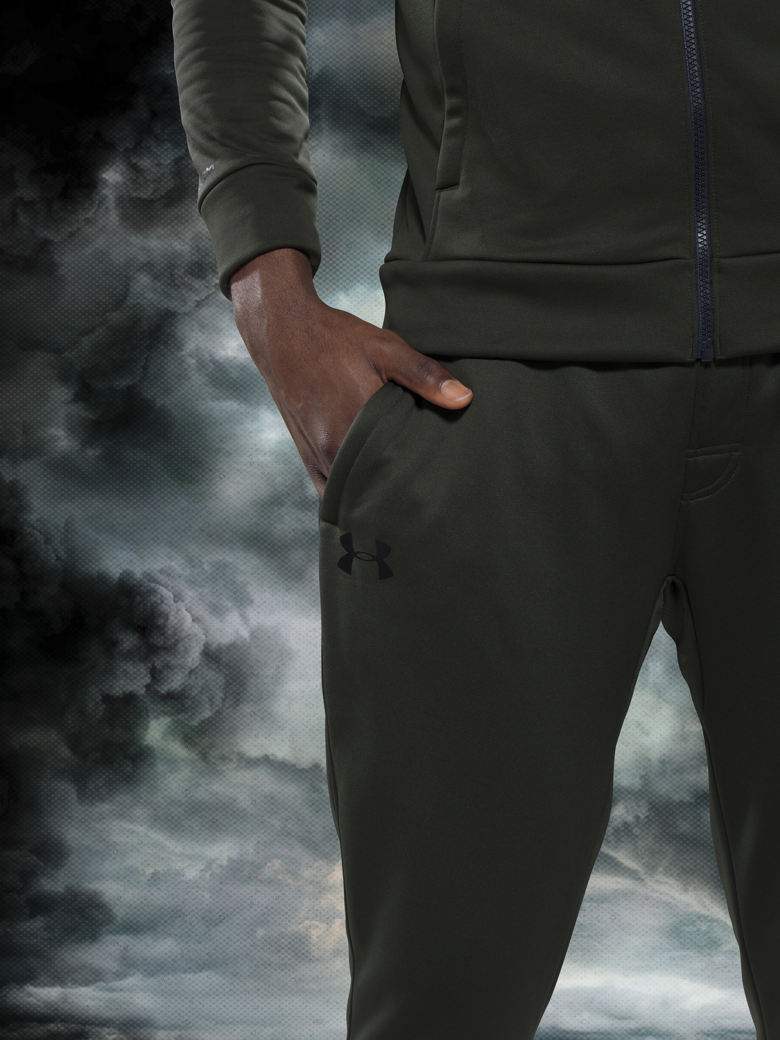 olive green under armour tracksuit on a stormy background