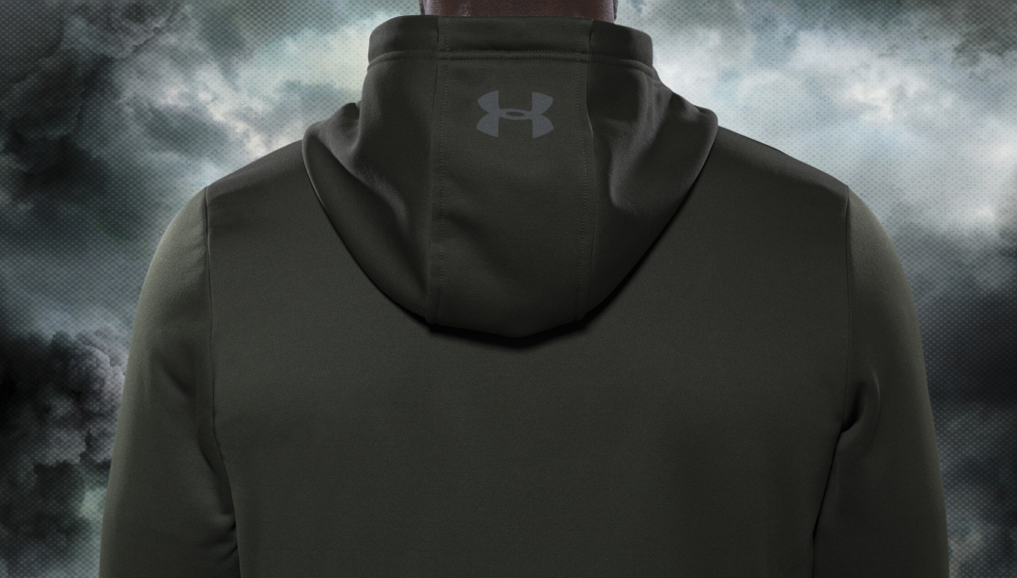 back view of an olive green under armour track top on a stormy background