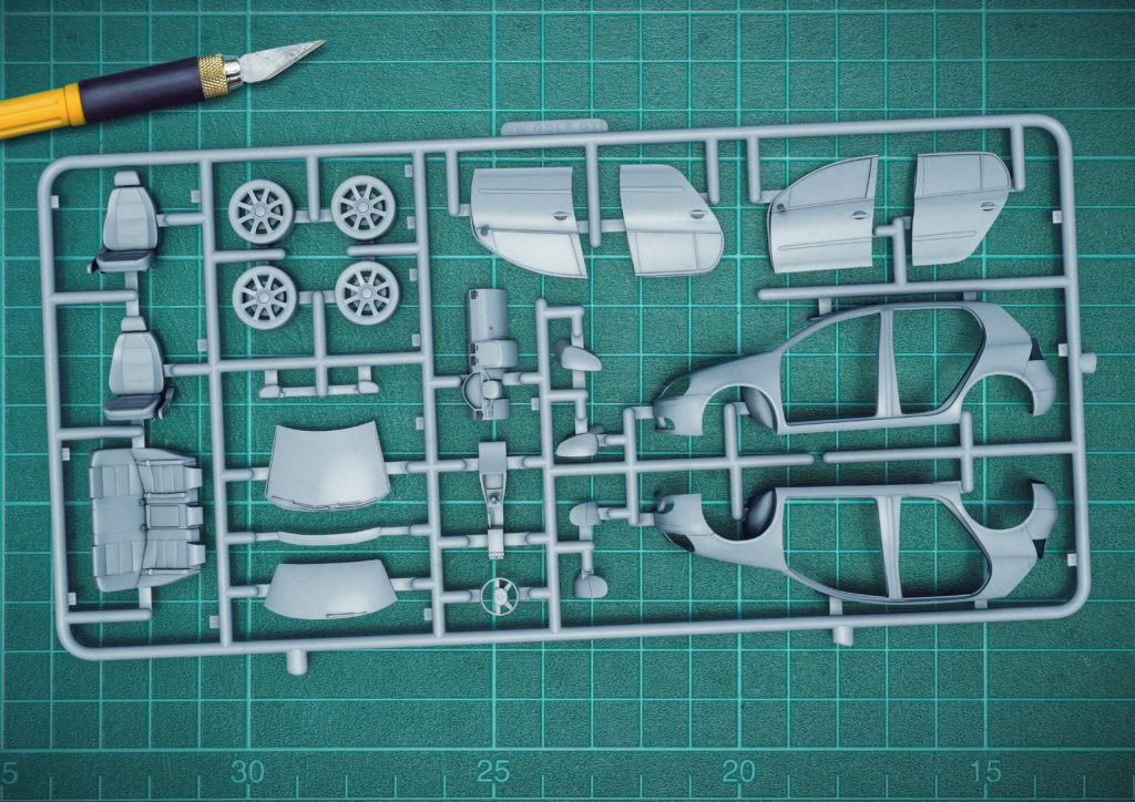 cgi illustration of an airfix model of a VW golf on a green cutting mat