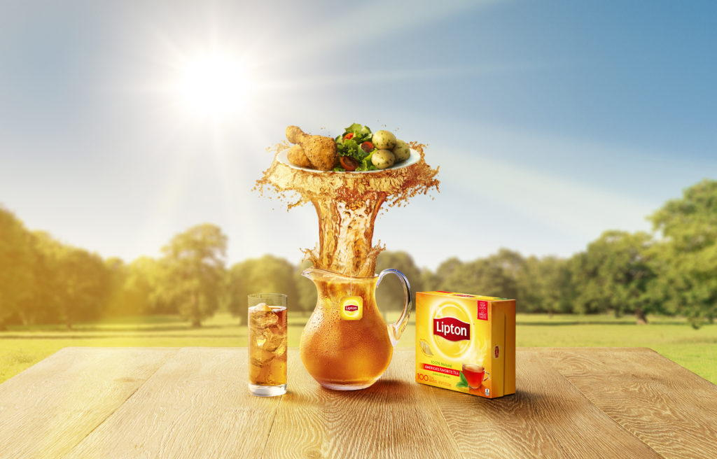a jug full of lipstons iced tea splashing upwards with a plate of food ontop