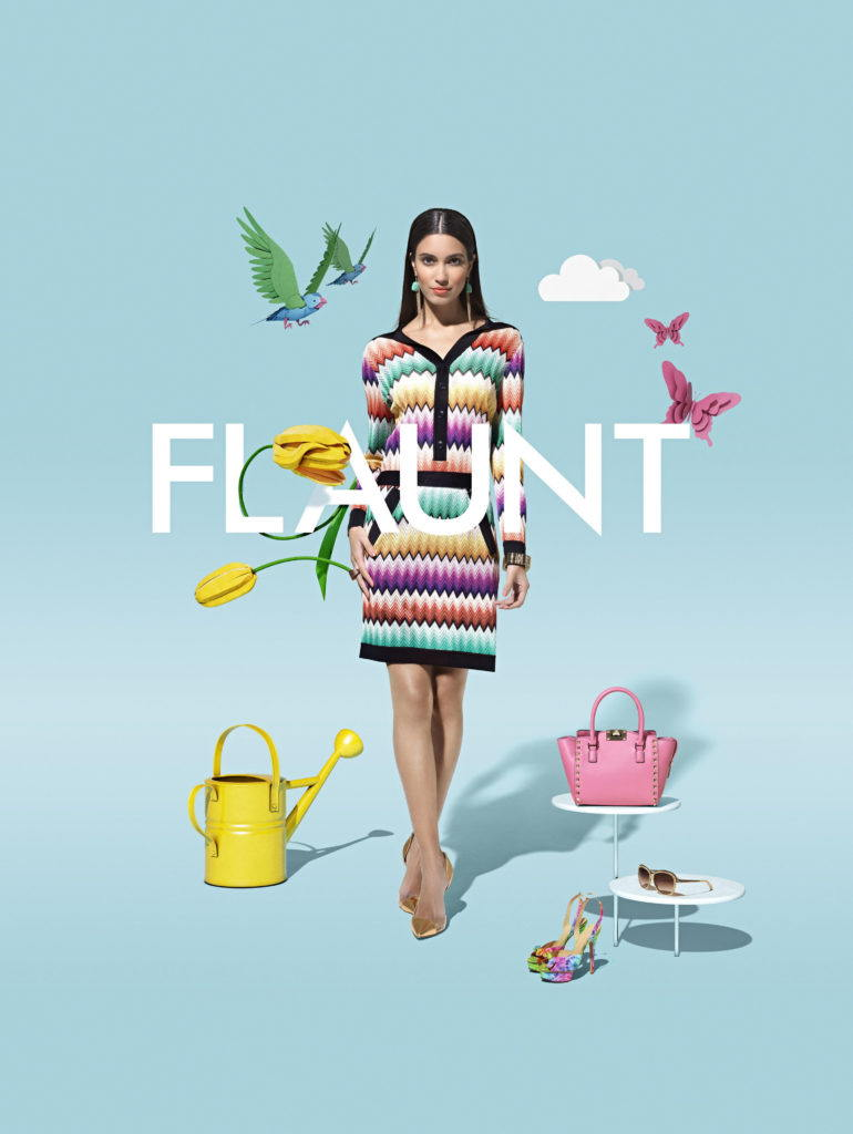 fashion model surround by paper sculture and a watering can handbag shoes and glasses with the word flaunt on a blue background