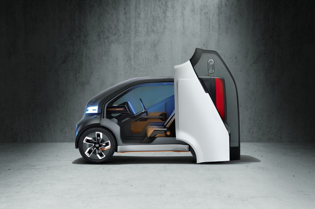 Honda neu-v car with door open in a concrete environment