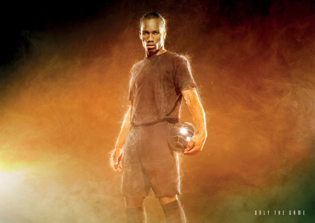 Drogba kicking a ball within a smokey environment